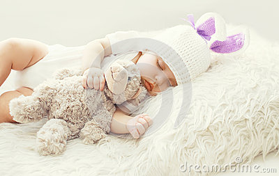 Cute baby sleeping with teddy bear toy on white soft bed home Stock Photo