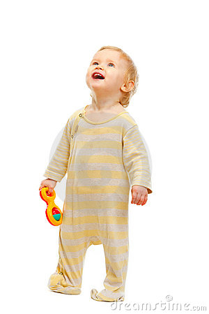 Free Cute Baby Standing With Rattle And Looking Up Stock Image - 23110061