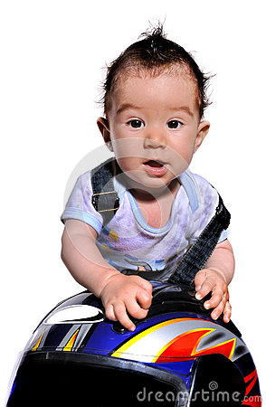 Cute baby  uses motorcycle helmet