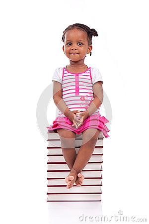 Cute black african american little girl seated in a stack of boo