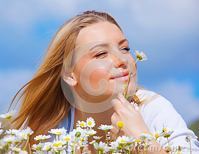 Cute female enjoying daisy smell