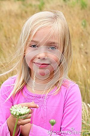 Cute blond girl in the grass.