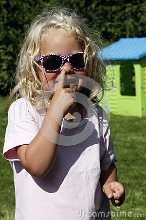 Cute blond girl picking her nose