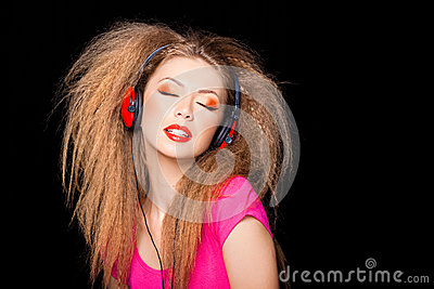 Cute blonde girl listening music on big headphones