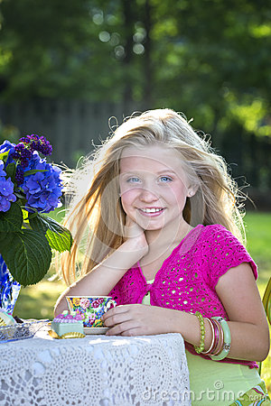 Cute blonde girl at outdoor tea party