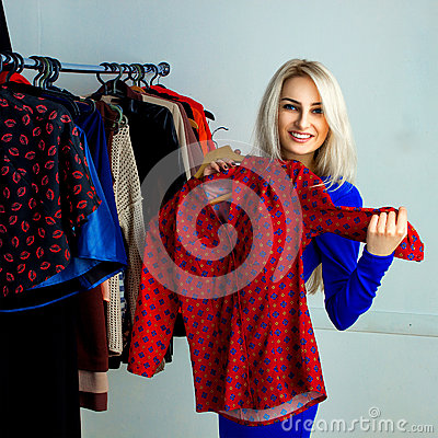 Free Cute Blonde Girl Smiling And Choosing Red Shirt In Clothing Stor Royalty Free Stock Photo - 67103575