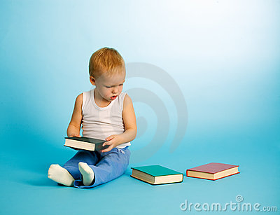 Cute boy chooses what to read from three books