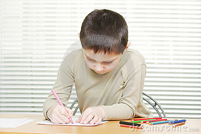 Cute boy at desk drawing with crayons