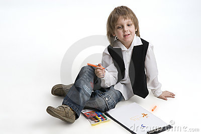 Cute boy drawing with crayons
