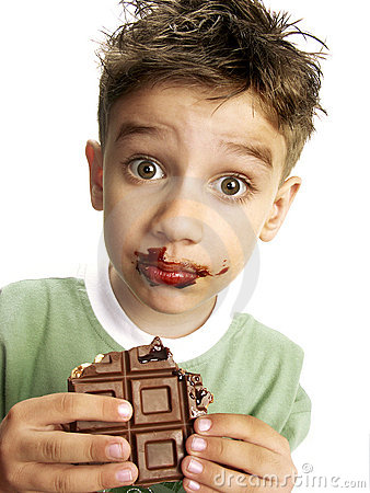Cute boy eating chocolate