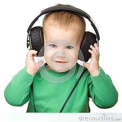 Free Cute Boy Enjoying Music Using Headphones Royalty Free Stock Photo - 23127375