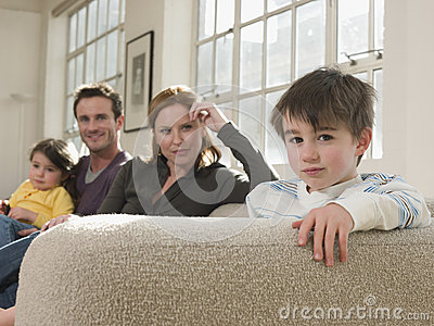 Cute Boy With Family Sitting On Sofa
