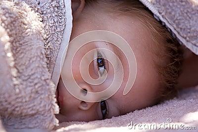 Cute boy hiding under towel