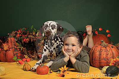 Cute boy and his dog in Halloween decoration