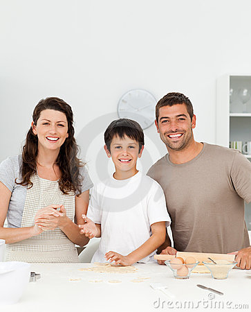 Cute boy with his parents in his kitchen