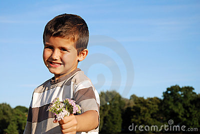Cute boy holding bunch of flowers