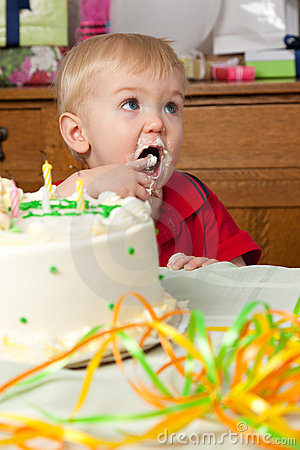 Cute boy licks frosting from fingers birthday cake