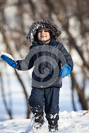 Cute boy playing with snow