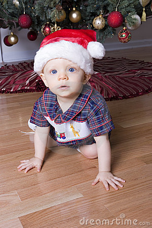 Cute boy playing under Christmas tree with santa hat
