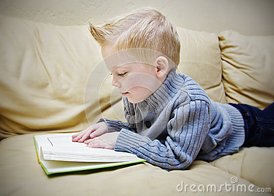Cute boy reading a book on the couch