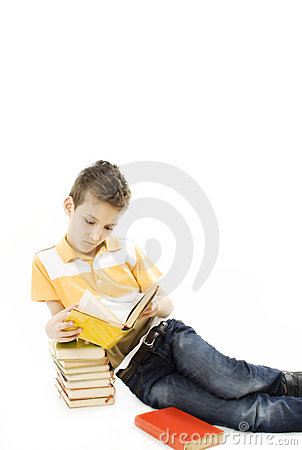 Cute boy reading a book on the floor