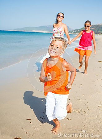 Cute boy with sister and mother on the beach