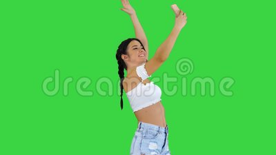 Cute brunette girl takes a selfie and dancing on a green screen, chroma key. Medium shot. Cute brunette girl takes a selfie and dancing on a green screen stock video footage