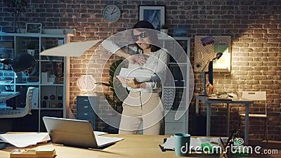 Cute Business Lady som dansar på kontoret på natten och slänger papper med kul lager videofilmer