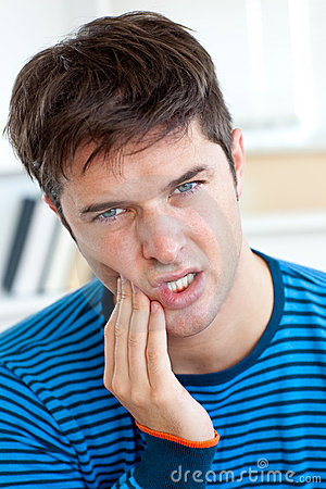 Cute caucasian man having a toothache at home