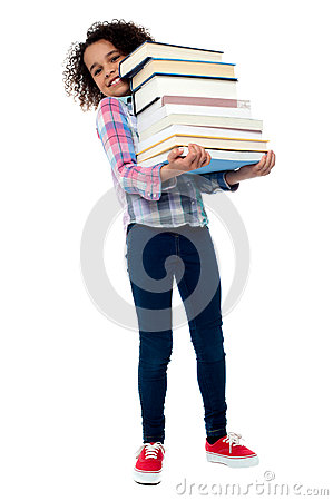 Cute cheerful child carrying stack of books