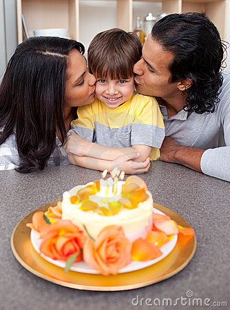 Cute child celebrating his birthday with parents