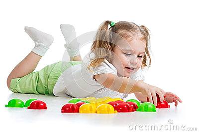 Cute child girl playing with mosaic toys