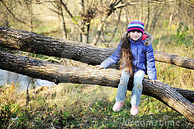 Cute child girl sitting on a tree branch