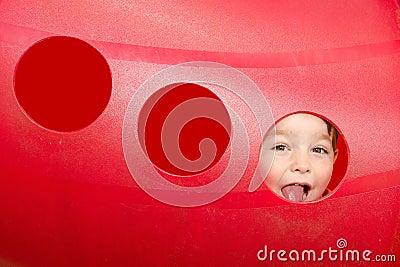Cute child peeks through hole at playground