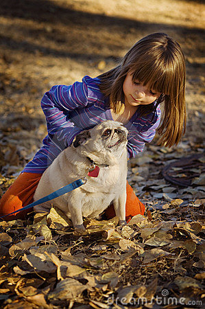 Cute child playing with pug dog autumn