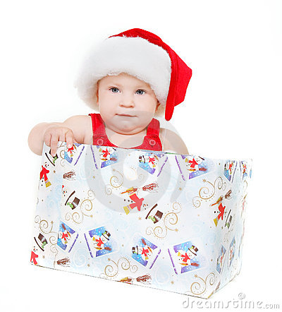 Cute child in santa hat sitting in gift box