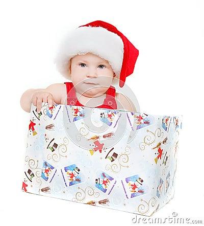 Cute child in santa hat sitting in gift box
