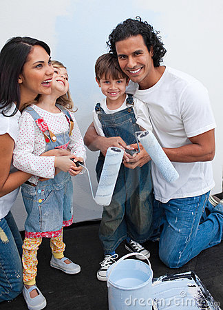 Cute children painting a room with their parents