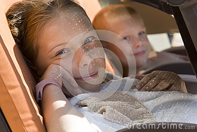 Cute children rests under a shade of a sunbed