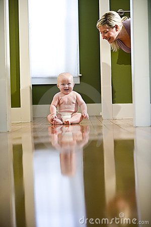 Cute chubby baby on floor laughing at mom
