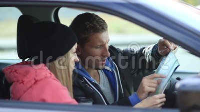Cute couple in car looking for the right direction stock footage