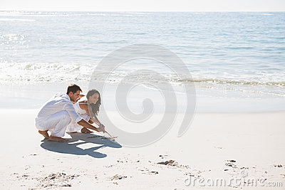 Cute couple drawing in the sand