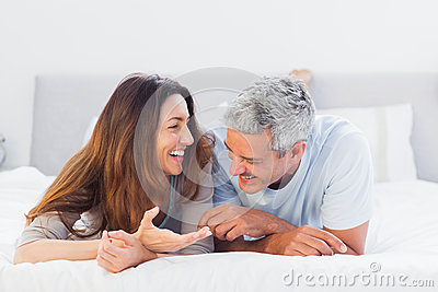 Cute couple lying on bed talking together