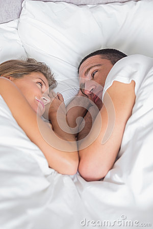 Cute couple lying together in bed