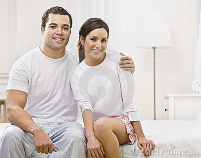 Cute Couple Sitting Together in their Bedroom