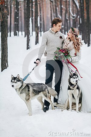 Free Cute Couple With Two Siberian Husky Are Posed On Background Of Snowy Forest. Winter Wedding. Artwork Stock Photos - 105074993