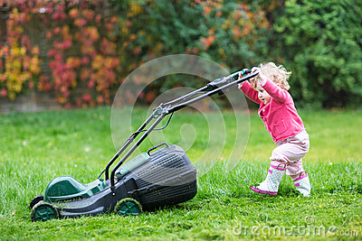 Cute curly baby girl with lawn mower in the garden