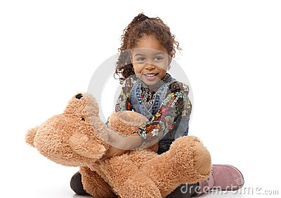 Cute ethnic girl playing with plush bear smiling