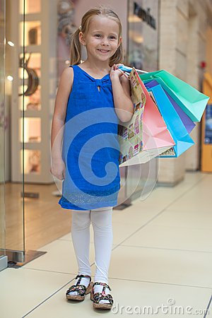 Cute fashion girl holding shopping bags and