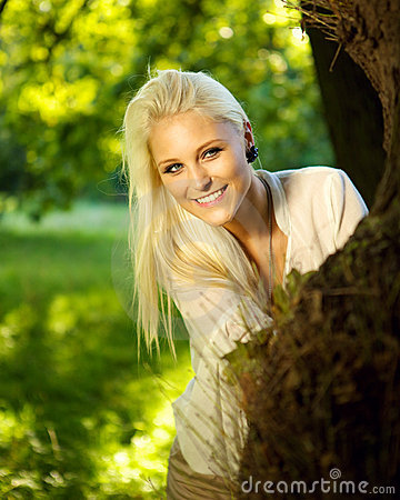 Cute female hiding behind a tree